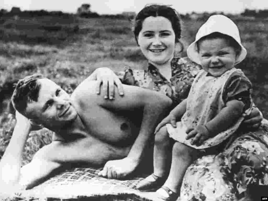 Советский космонавт Юрий Гагарин на пляже с женой Валентиной и дочерью Еленой в июне 1960 года, менее чем за год до того, как он вошел в историю как первый человек, совершивший полет в космос