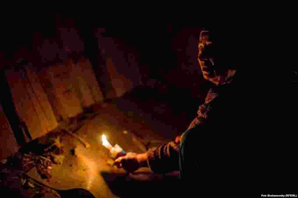 Женщина показывает неразорвавшийся снаряд, застрявший в полу ее дома. Дебальцево