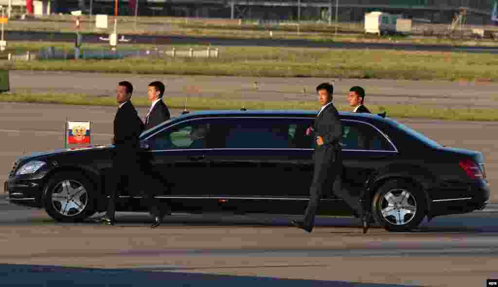 Китайские службы безопасности охраняют лимузин президента России Владимира Путина, прибывшего в Пекин. 2 сентября 2015