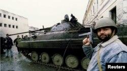Сторонник Ичкерии осматривает танк российских войск в Грозном. 4 января 1995 года
