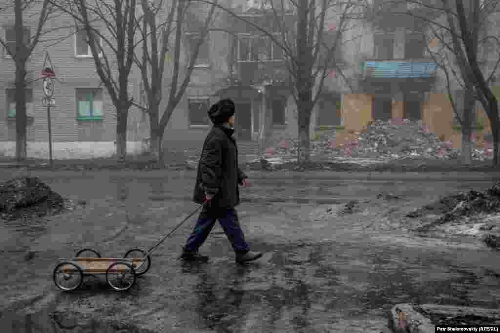 Мужчина с тележкой проходит мимо разрушенного здания