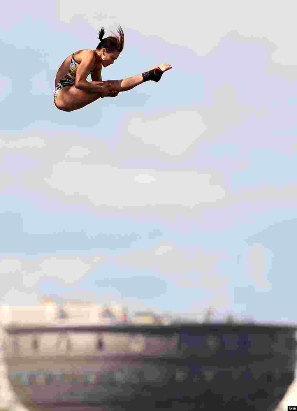 К сожалению, во время тренировки одна из участниц неудачно приземлилась на воду из-за чего не смогла выступить на самом чемпионате На фото - немецкая спортсменка Анна Бадер прыгает с 20 метров