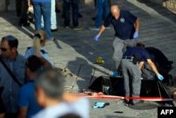 Израильские силы безопасности осматривают тело человека, который пытался осуществить нападение с ножом на Дамасские ворота у входа в Старый город в Восточном Иерусалиме, 14 октября 2015