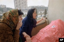 Two Azerbaijani women in Baku are overcome with grief during a funeral for a relative on January 28, 1990.