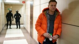 RUSSIA -- Russian opposition leader Aleksei Navalny stands near law enforcement agents in a hallway of a business centre, which houses the office of his Anti-Corruption Foundation (FBK), in Moscow, December 26, 2019