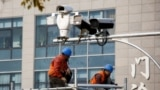 China - Men work on top of a scaffolding underneath CCTV surveillance cameras in Beijing
