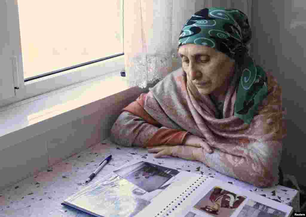 Патимат Сулейманова, тетя братьев Царнаевых, смотрит на фотографии из семейного альбома в своем доме в Махачкале.