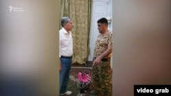 Former President Almazbek Atambaev negotiates surrender terms with Deputy Interior Minister Kursan Asanov on August 8, 2019. (Radio Azattyk)