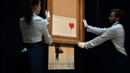 "U.K. -- Sotheby's employees pose with the newly completed work by artist Banksy entitled ""Love is in the Bin"", a work that was created when the painting ""Girl with Balloon"" was passed through a shredder in a surprise intervention by the artist, at Sotheby"