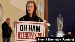 "Holding a poster that reads ""He's not our tsar,"" a Moscow activist stages a one-person protest against proposed constitutional amendments that would allow Russian leader Vladimir Putin to run for an additional two terms as president."