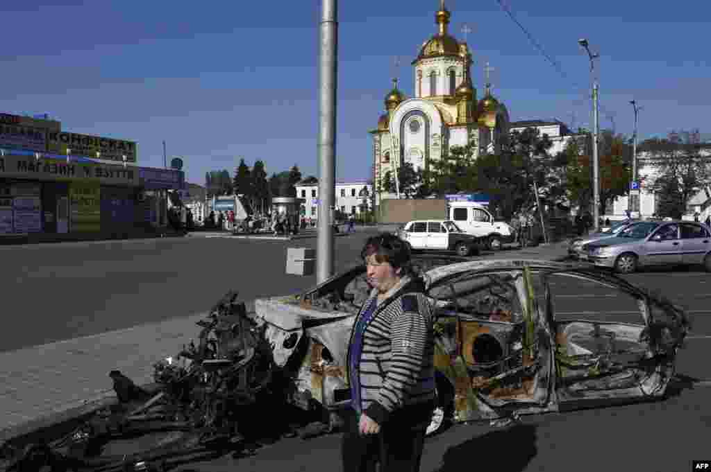Ukraine -- A woman walks past a burnt car near the railway station in Donetsk, September 15, 2014