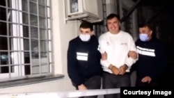 Video footage released by the Georgian Interior Ministry on October 1 showed a handcuffed Mikheil Saakashvili being escorted by police into an unidentified building.