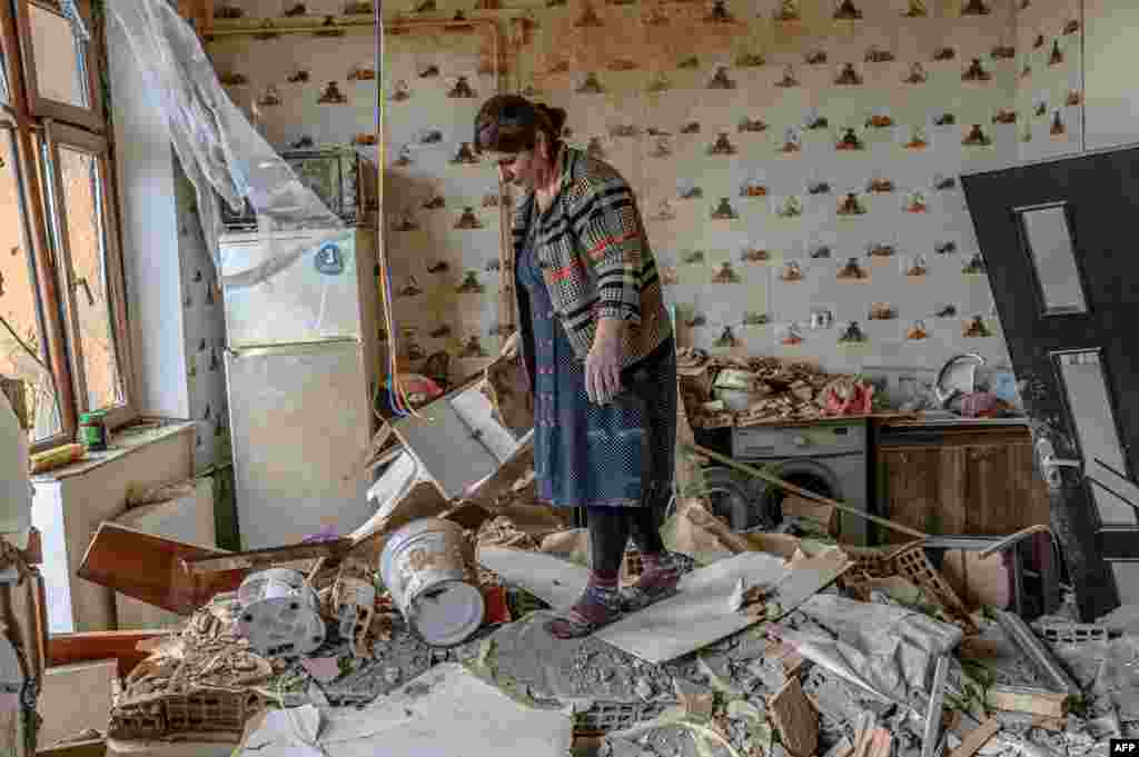 Khatira Celilova walks in the kitchen of her destroyed apartment in the Azerbaijani town of Tartar  following an October 10, 2020 ceasefire in the fighting over the breakaway region of Nagorno-Karabakh and seven surrounding Armenian-occupied territories. Residents had evacuated the town, located just to the east of Nagorno-Karabakh, after heavy shelling.