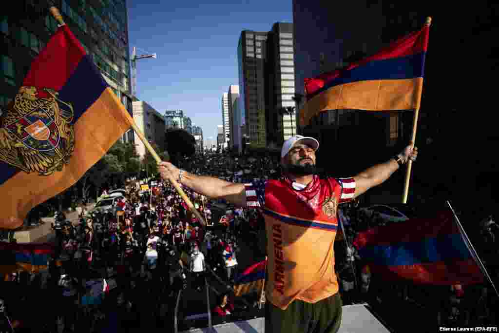 Arkady Grigorian stands on the roof of an RV waving Armenian flags as thousands of American-Armenian protesters march in front of Turkey's consulate in Los Angeles, California on October 11.  Southern California is estimated to contain the world's largest Armenian diaspora.