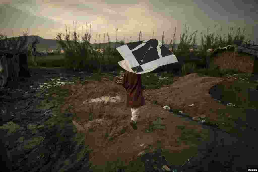 Мальчик запускает воздушного змея в пригороде Исламабада, Пакистан