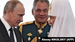 Владимир Путин с патриархом Кириллом и главой Минобороны Сергеем Шойгу