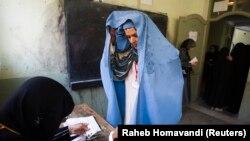 Афганская женщина показывает свое лицо сотруднице избирательной комиссии во время выборов. 18 сентября 2010 года