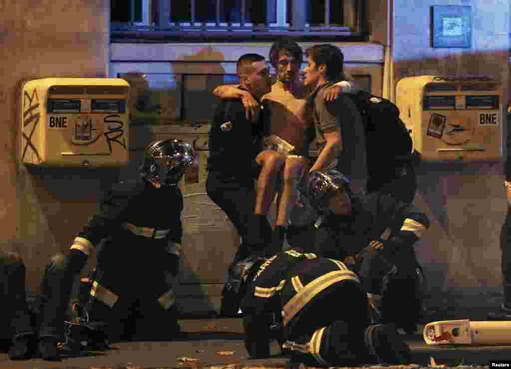 """Полицейские помогают раненному человеку рядом с концертным залом """"Батлакан"""""""