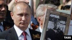 Президент России Владимир Путин с портретом своего отца, который дружил с Виктором Колбиным, отцом бывшего совладельца Gunvor Петром Колбиным