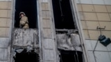 RUSSIA - A firefighter looks out from inside the fire-gutted shopping mall in the industrial city of Kemerovo in western Siberia on March 29, 2018