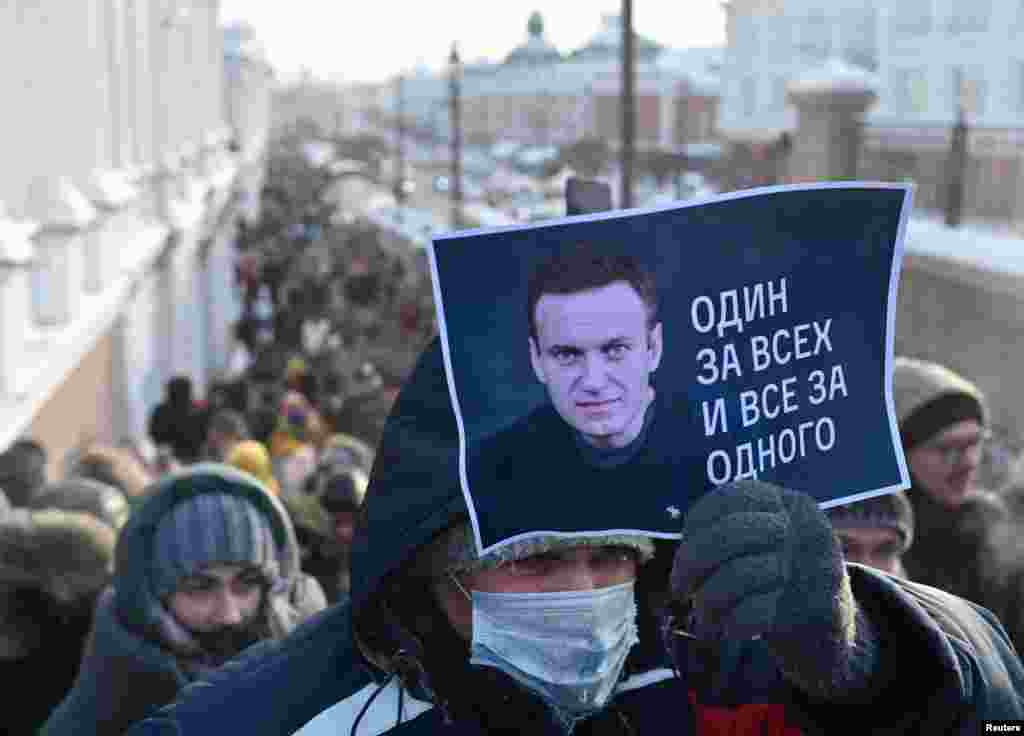 "In Omsk, a man holds a placard with Aleksei Navalny's photo and the slogan ""All for one and one for all."""