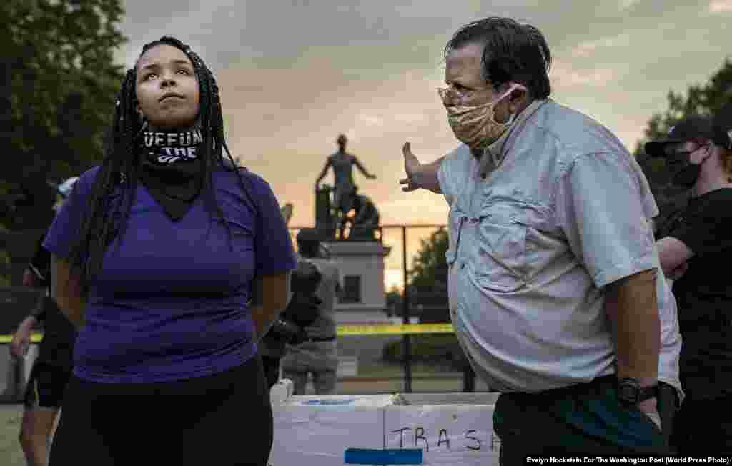 """Мужчина и женщина спорят о сносе памятника, посвященного Прокламации об освобождении рабов Авраама Линкольна, в Вашингтоне, США (25 июня 2020). Первое место в категории""""Срочные новости"""", автор –Эвелин Хокстин"""