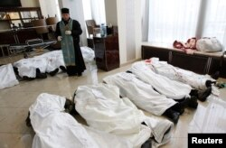 A priest stands in the lobby of the Hotel Ukraine, surrounded by the bodies of Euromaidan protesters killed during clashes with riot police in Kyiv on February 20, 2014.