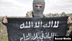 "Член ""Исламского государства"", известный как ""Абдулла Таджик"", держит в руках флаг, на котором написано ""Талибан в земле Леванта"""