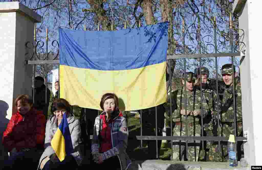 В поселке Любимовка украинские военнослужащие собираются на территории воинской части. Их родственники сидят у забора, чтобы не допустить вооруженных столкновений, 3 марта 2014