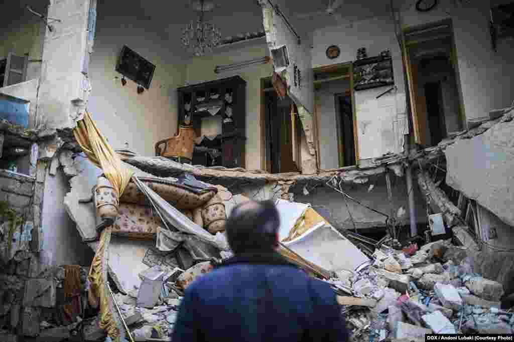 Мужчина смотрит на дом, разрушенный после рейда войск Башара Асада в Алеппо (Сирия). Район аль-Изаа был одним из густонаселенных во всем городе. Во время боев он был сильно разрушен. Фото сделано 3 января 2013 года