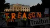 """U.S. -- Activists hold letters reading the word """"Treason"""" in front of the White House during a sunset demonstration to denounce the link between the 2016 Trump campaign and Russia, in Washington, July 29, 2018"""