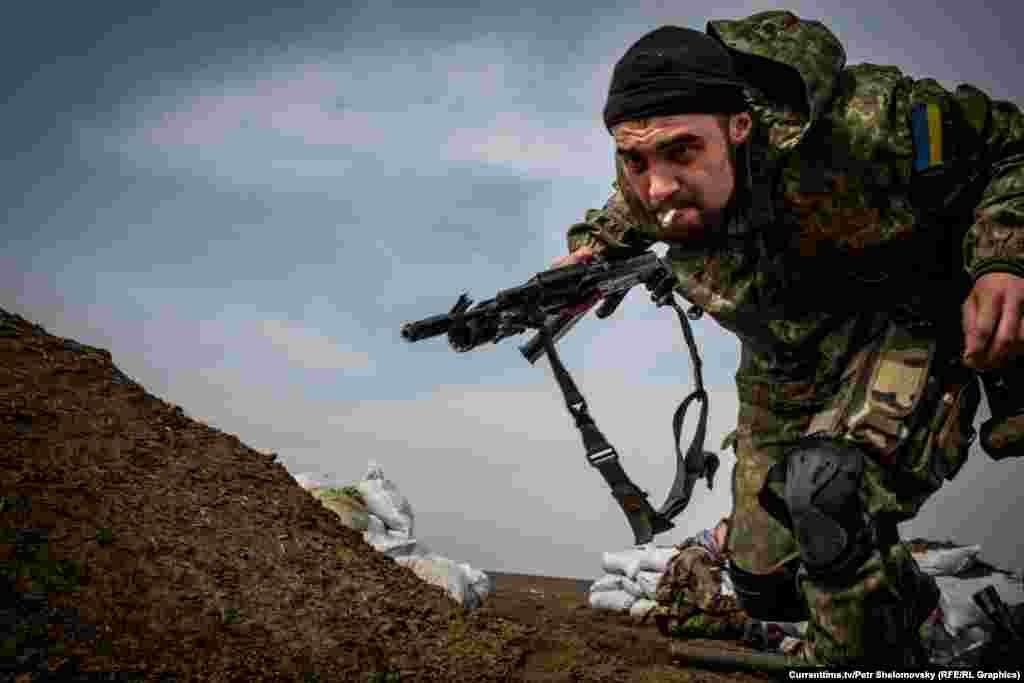 """Украинский боец батальона """"Азов"""" пытается укрыться от шквального огня противника. Посело Широкино вблизи Мариуполя. 18 апреля 2015"""