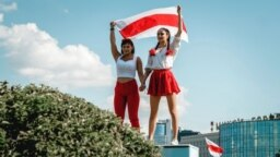Two women display a former Belarusian national flag, a symbol of opposition to the government, during a Minsk rally on August 16, 2020 against police violence and Belarus' official presidential election results.