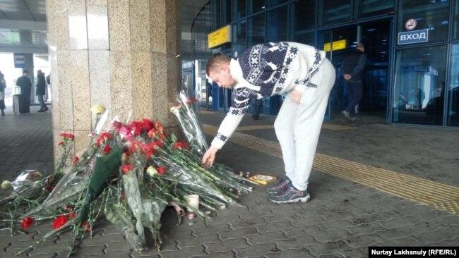 Люди оставляют цветы у здания пассажирского терминала алматинского аэропорта, рядом с которым разбился пассажирский самолет. 28 декабря 2019 года