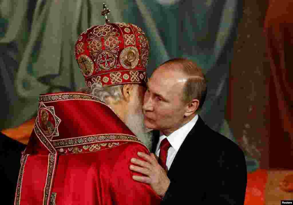 После службы: президент РФ Владимир Путин обнимает патриарха Кирилла в Храме Христа Спасителя в Москве