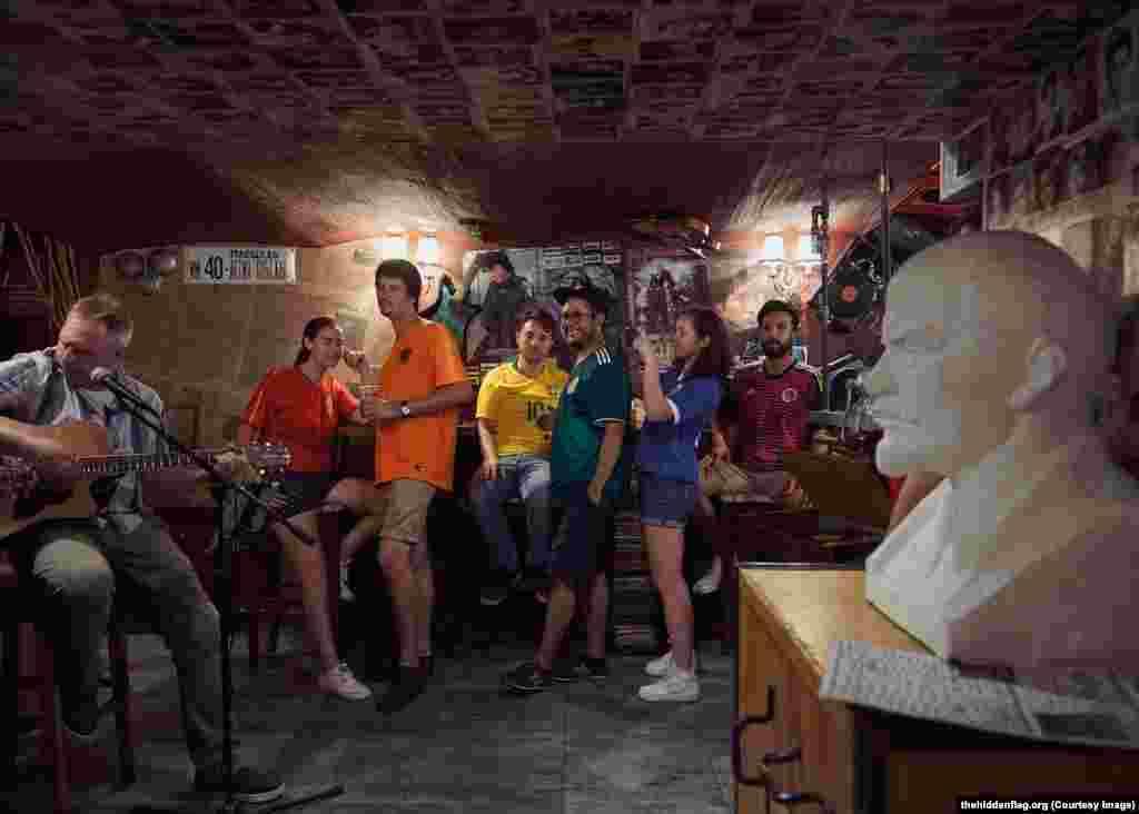 """Группа в баре около бюста Ленина. Бразилец Элой Перозан-младший (в желтом) говорит, что его парень предупреждал об опасности агитировать за права геев в России, но Элой не переживал. """"Это проект, в котором я очень хотел принять участие, – сказал он. – Это призыв к любви"""""""