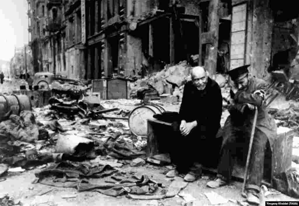 """Слепой мужчина (справа) с проводником на разрушенной улице Берлина в 1945 году. Халдей вспоминал, что спросил мужчину на немецком, откуда они пришли. Слепой ответил: """"Мы больше не знаем. Мы не знаем, откуда мы пришли, или куда мы идем"""""""