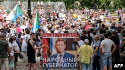 "Demonstrators in Khabarovsk, Russia on July 25, 2020 carry a poster that calls for the return of former Governor Sergei Furgal, dubbed ""The People's Governor."""