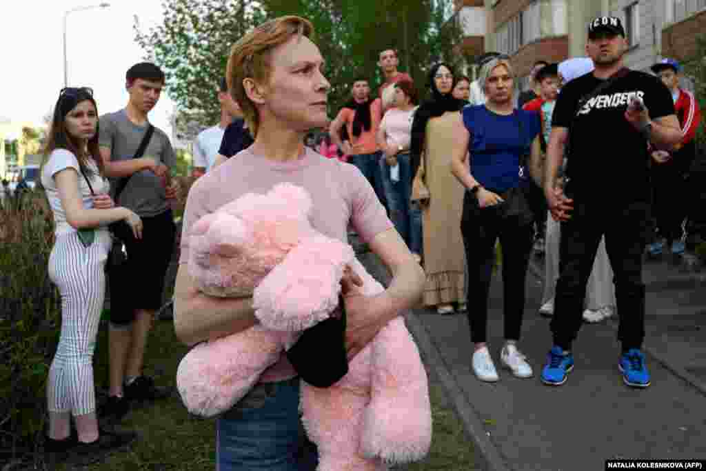 People gather near School No. 175 after the May 11, 2021 shooting there. One woman carries a stuffed animal perhaps either to commemorate the seven children killed in the attack or to donate for the 18 children wounded.