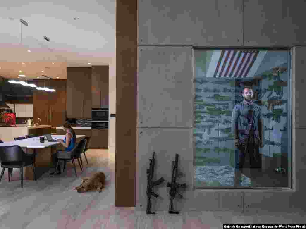 """Роберт Болдвин-младший в оружейной комнате в своем доме в Лас-Вегасе (16 апреля 2019). За столом работает его девушка. Первое оружие – винтовку 22-го калибра – ему подарил отец, когда Роберту было 6 лет. Первое место в категории""""Портрет, фоторепортаж"""", автор –Габриэль Галимберти"""