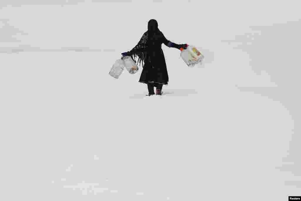 Афганская девочка несет пустые контейнеры для воды во время снегопада в Кабуле, 6 февраля(Reuters/Mohammad Ismail)