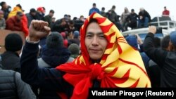 A demonstrator wearing the national flag in Bishkek gestures during an October 6, 2020 protest against the results of Kyrgyzstan's parliamentary election.