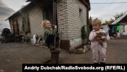 Seven-year-old Diana and 3-year-old Herman play outside a house 70 meters (230 feet) from a Ukrainian army frontline position in the Donetsk region in 2019.