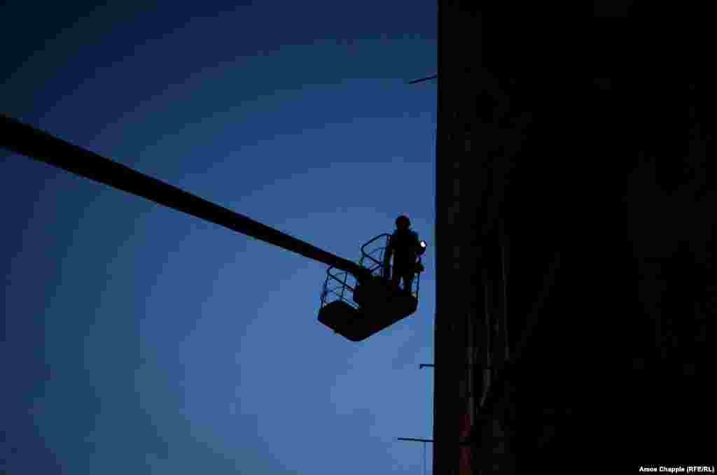 Несмотря на то, что он вне зоны досягаемости снайперов, ван Хелтен ждет наступления темноты, чтобы дорисовать самые высокие, наиболее открытые части мурала