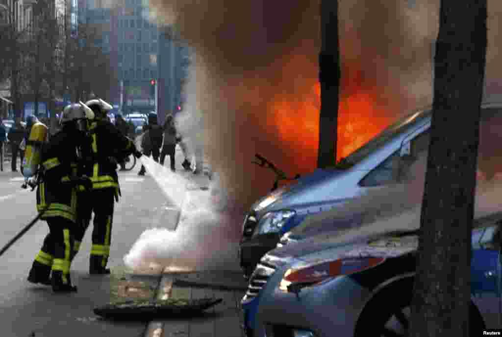 Пожарные тушат один из полицейских автомобилей, подожженных прямо у нового здания Европейского центробанка