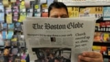 U.S. -- Phillip Minias, 46, owner of Snax Express, reads the Boston Globe, in Boston, Massachusetts, August 15, 2018