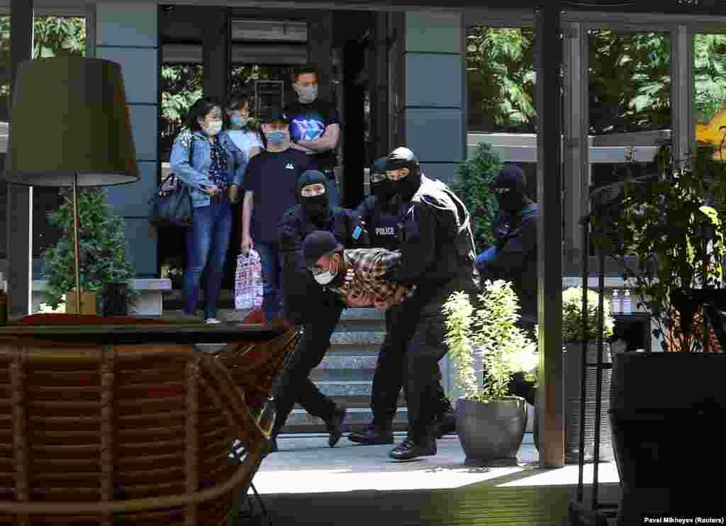 Сотрудники спецназа несут задержанного в автозак