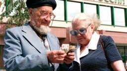 Russia -- a man and a woman count money in front of the Sberbank in Moscow on July 30, 1998