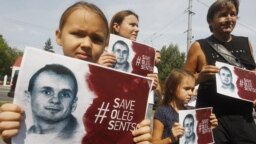 UKRAINE – Ukrainians hold posters with the hashtag '#Save Oleg Sentsov' during a rally on the 100th day Ukrainian film director Oleg Sentsov's hunger strike with protesters demanding his release, in front of the Russian embassy in Kyiv, 21 August 2018