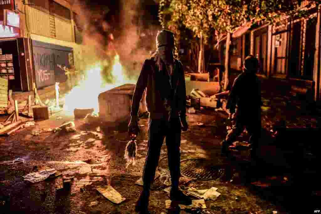 Курд, вооруженный бутылкой с зажигательной смесью, на фоне горящей баррикады во время столкновений с турецкой полицией в районе Гази в Стамбуле.